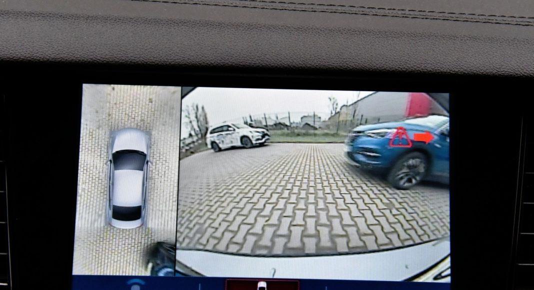 Kamera cofania ostrzega o zbliżającym się z boku pojeździe.